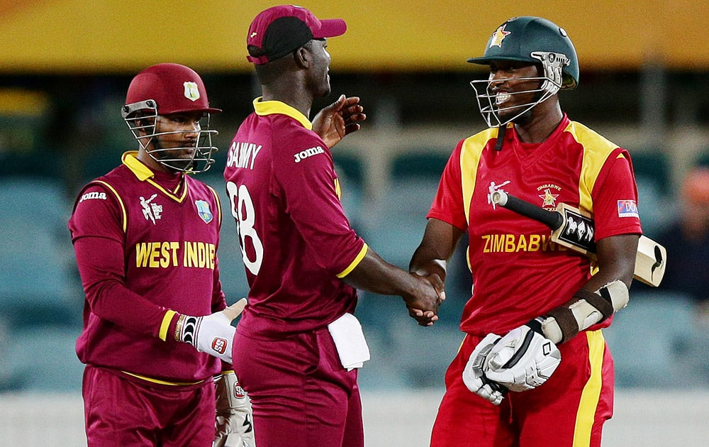 Zimbabwe's Tendai Chatara shakes hands with West Indies Darren Sammy West and Denesh Ramdin after their Cricket World Cup Pool B match in Canberra, Australia.