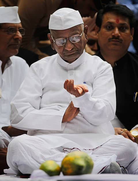 Anna Hazare looks at his watch as he sits on a stage during a protest against the government's proposed move to ease rules for acquiring land to facilitate infrastructure projects in New Delhi.