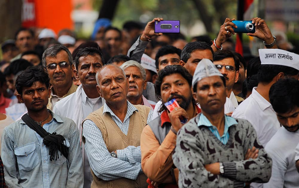 People listen to anti-corruption activist Anna Hazare as he leads a protest against the government's proposed move to ease rules for acquiring land to facilitate infrastructure projects in New Delhi.