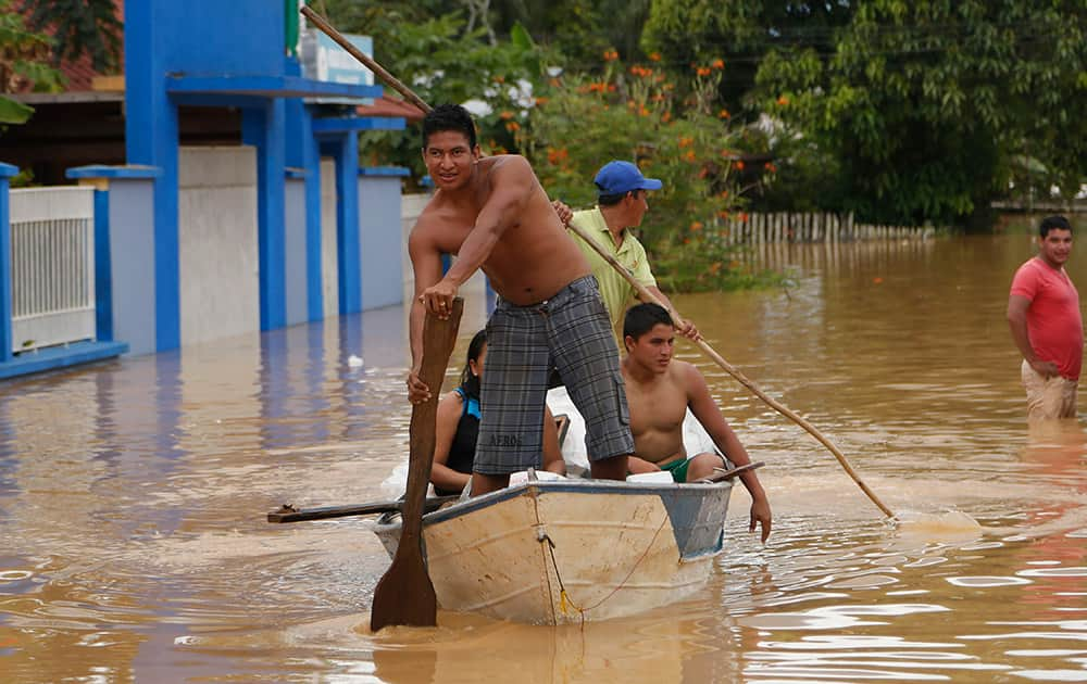 Men use a raft to navigate the flooded streets in Cobija, Bolivia.