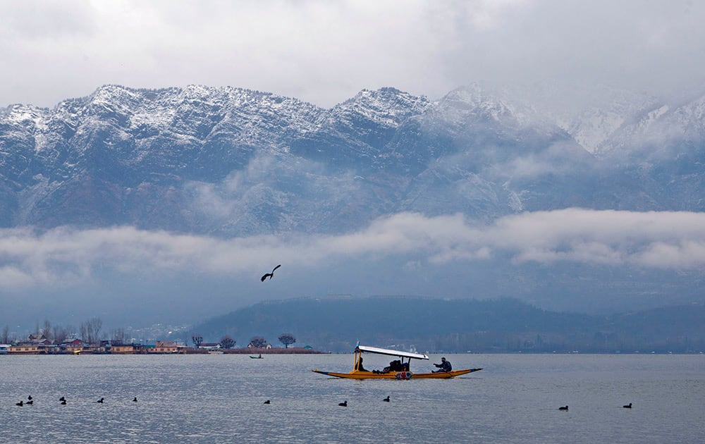 Tourists enjoy Shikara, a traditional wooden boat, with the backdrop of snow covered mountains at the Dal Lake in Srinagar.