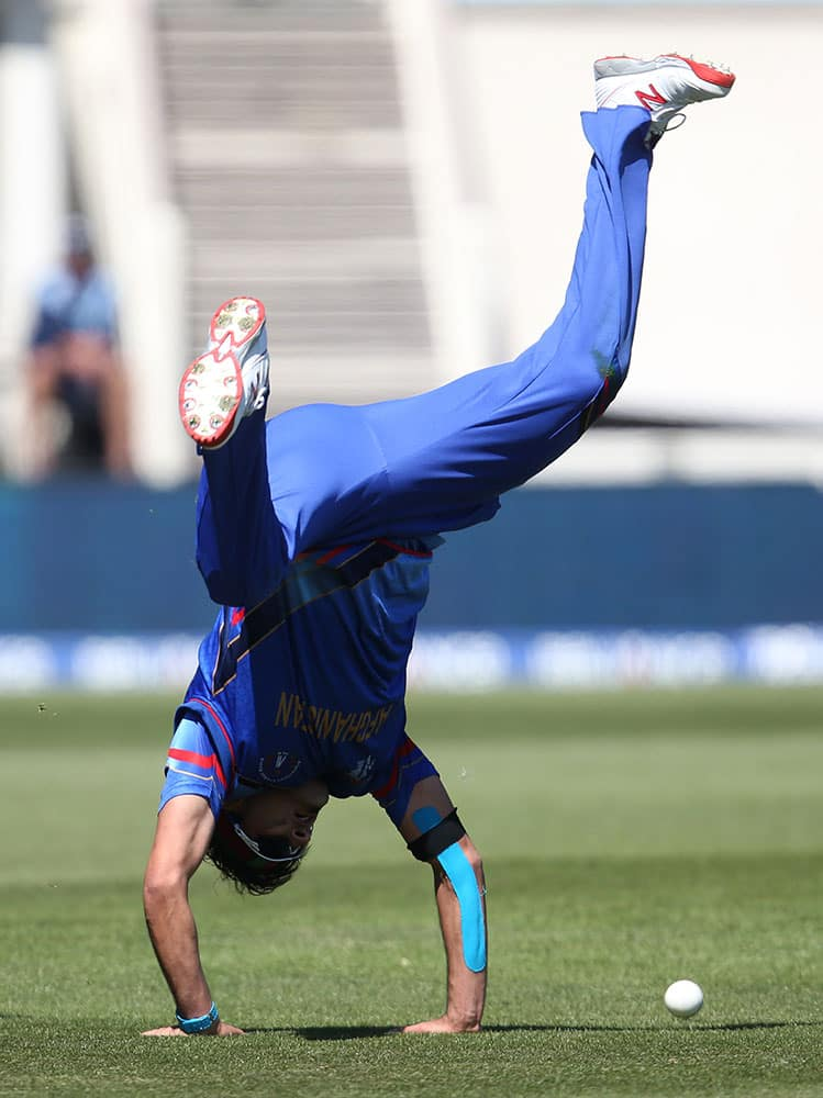 Afghanistan's Hamid Hassan does a hand stand as he reacts after taking a catch to dismiss Scotland's Josh Davey during their Cricket World Cup Pool A match in Dunedin, New Zealand.
