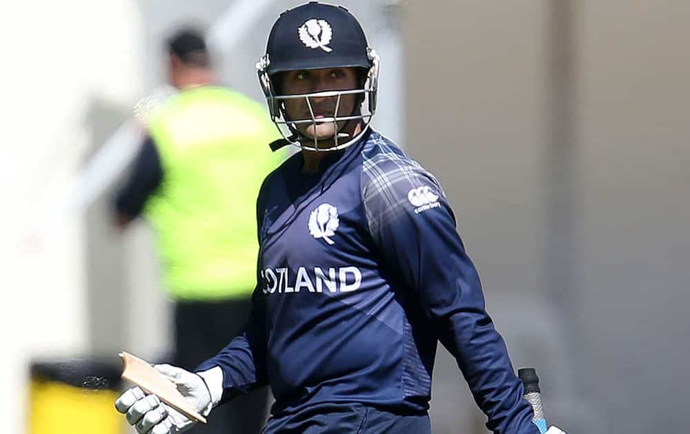 Scotland batsman Majid Haq holds a piece of his broken bat during their Cricket World Cup Pool A match against Afghanistan in Dunedin, New Zealand.