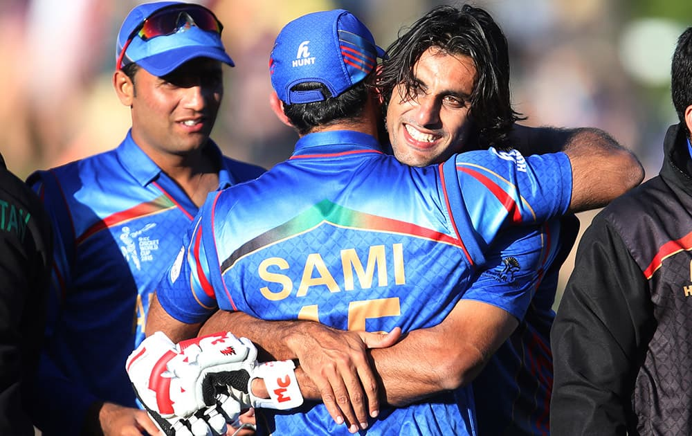 Afghanistan's Shapoor Zadran embraces teammate Samiullah Shenwari as he celebrates his team's Cricket World Cup Pool A win over Scotland in Dunedin, New Zealand.