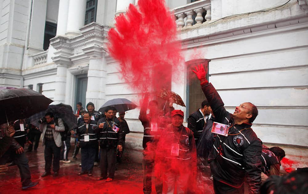 A Nepalese devotee throws vermillion powder after erecting Chir, a ceremonial pole, marking the beginning of Hindu festival of colors Holi, in Kathmandu, Nepal.