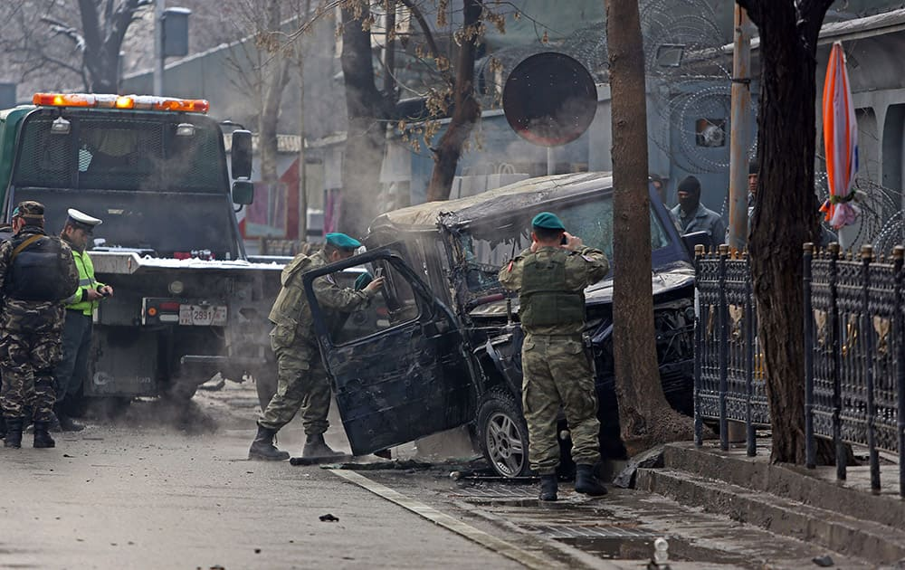 Turkish soldiers inspect a damaged vehicle at the site of a suicide attack in Kabul, Afghanistan. A suicide bomber driving a car packed with explosives targeted a Turkish Embassy vehicle near the Iranian Embassy in the Afghan capital during the Thursday morning rush hour.