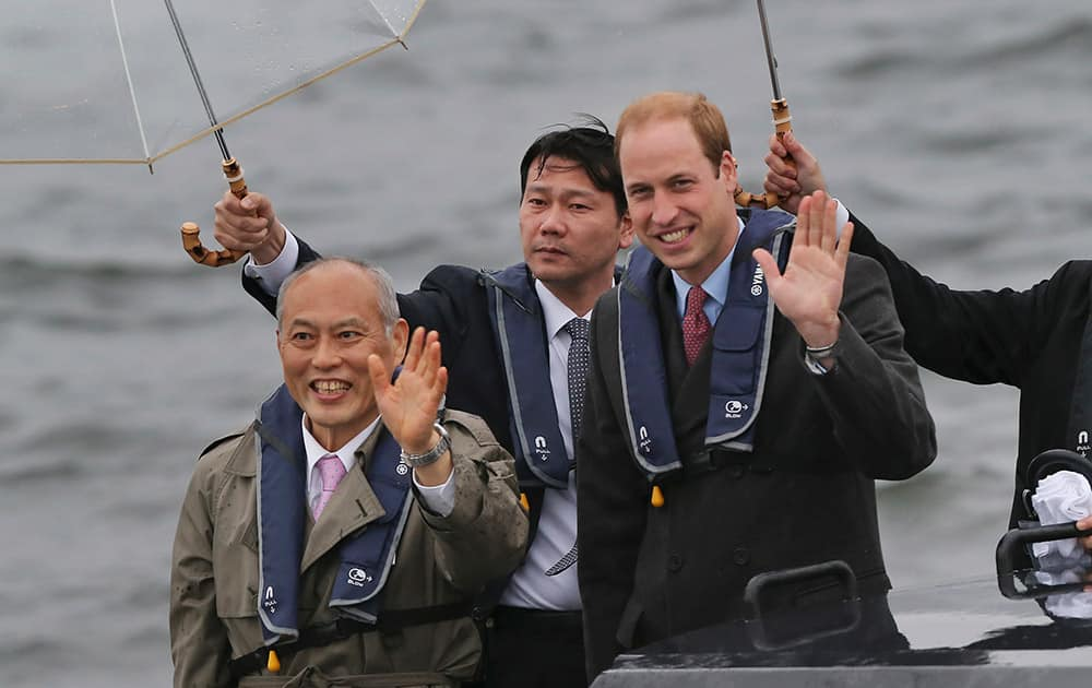 Britain's Prince William, waves with Tokyo Gov. Yoichi Masuzoe from a boat in Tokyo harbor after arriving in Tokyo. The Duke of Cambridge is on a four-day visit to Japan.