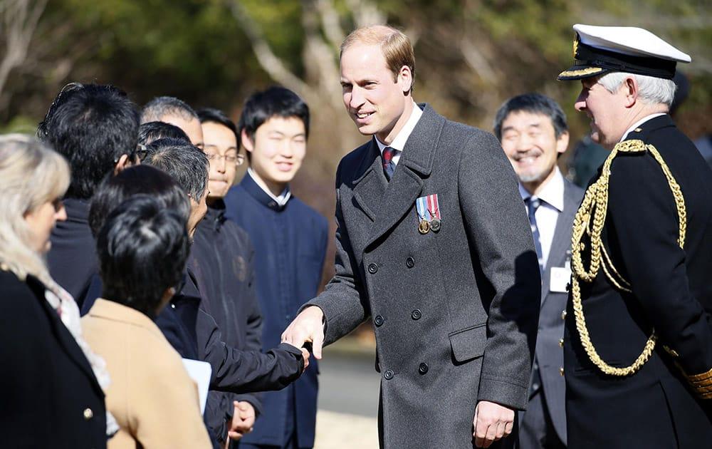 Britain's Prince William, talks people during his visit at Yokohama War Cemetery in Yokohama, near Tokyo. William is on his first visit to Japan.