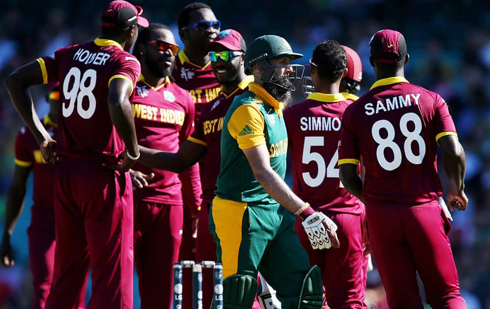 South Africa's Hashim Amla walks from the field as West Indies players celebrate his dismissal during their Cricket World Cup Pool B match in Sydney, Australia.