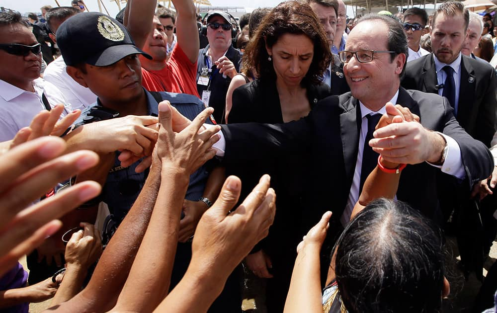 French President Francois Hollande, front right, is greeted by the crowd during his visit to the typhoon-ravaged Guiuan township, Eastern Samar province in central Philippines.