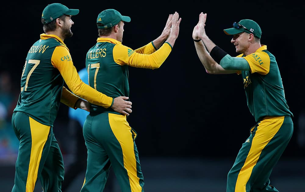 South Africa's AB De Villiers is congratulated by teammates Dale Steyn and Rilee Rossouw after taking a catch to dismiss West Indies Jonathan Carter during their Cricket World Cup Pool B match in Sydney, Australia.