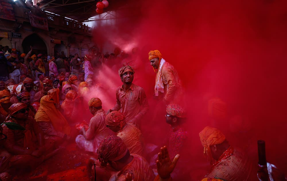 Hindu men from the village of Nandgaon throw colored powder at each other as they play holi at the Ladali or Radha temple before taking out a procession for the Lathmar Holi festival at the legendary hometown of Radha, consort of Hindu God Krishna, in Barsana.