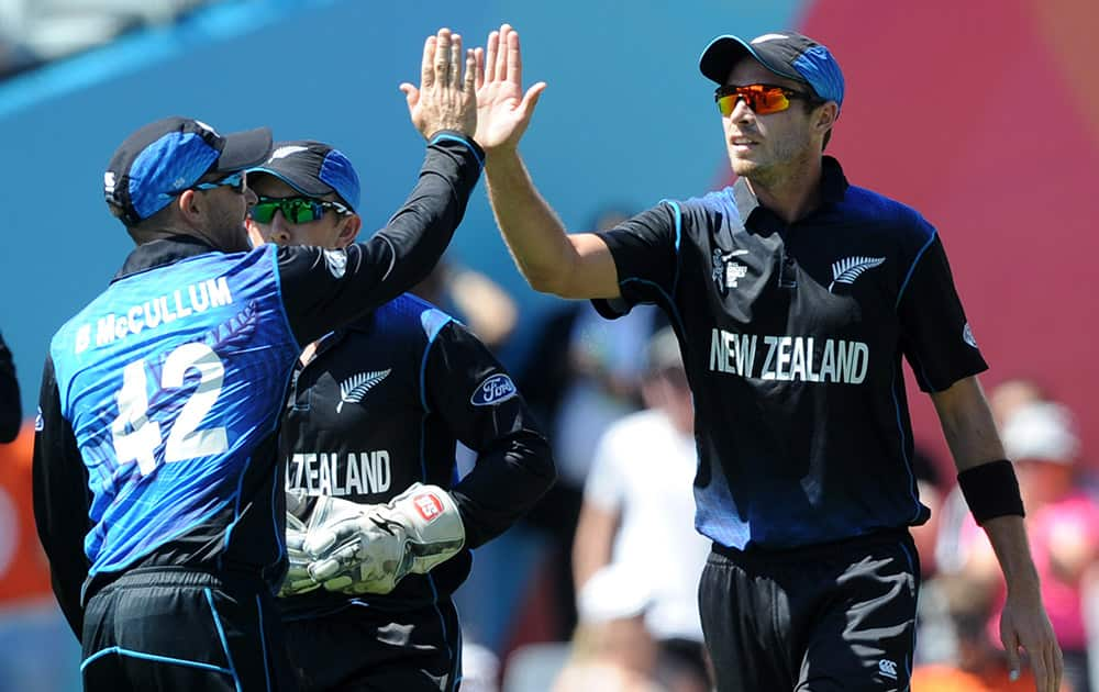New Zealand's Tim Southee, right, is congratulated by his captain Brendon McCullum after taking a catch to dismiss Australian batsman Shane Watson during their Cricket World Cup match in Auckland.