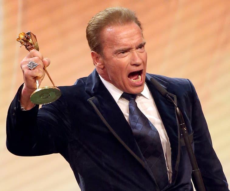 Arnold Schwarzenegger holds a Golden Camera lifetime achievement award during awarding ceremony in Hamburg, northern Germany.