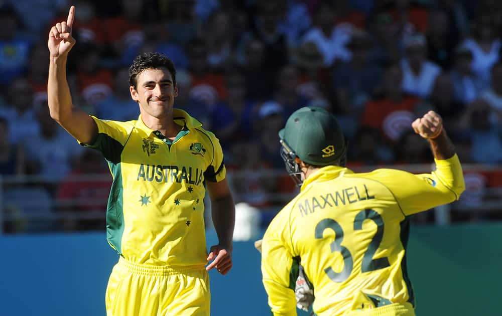 Australia's Mitchell Starc celebrates with teammate Glenn Maxwell after taking the wicket of New Zealand's Ross Taylor during their Cricket World Cup match in Auckland, New Zealand.