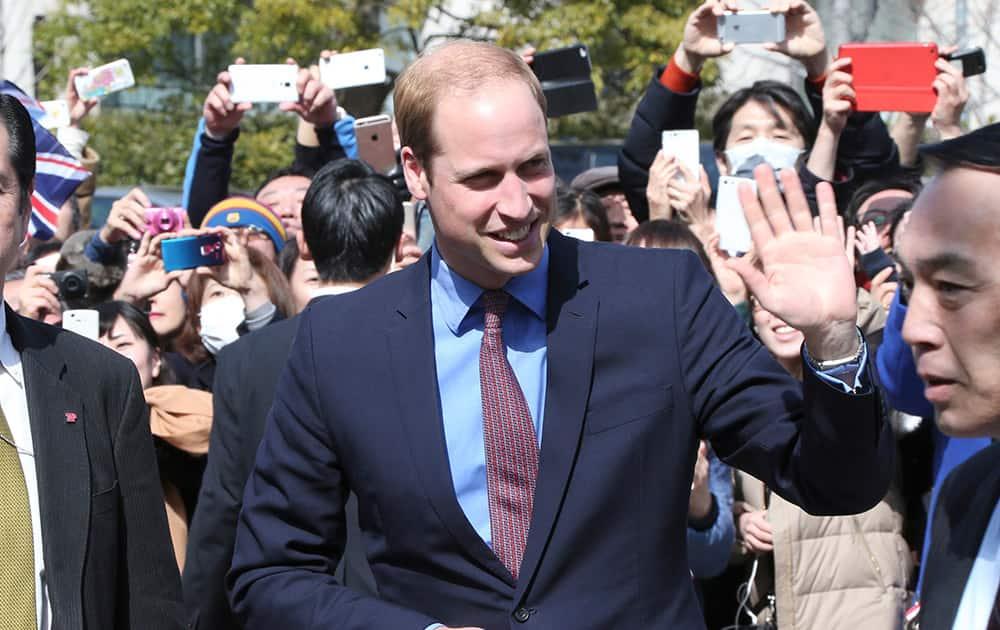 Britain's Prince William waves upon arrival at the Tsutaya bookstore at Daikanyama in Tokyo.