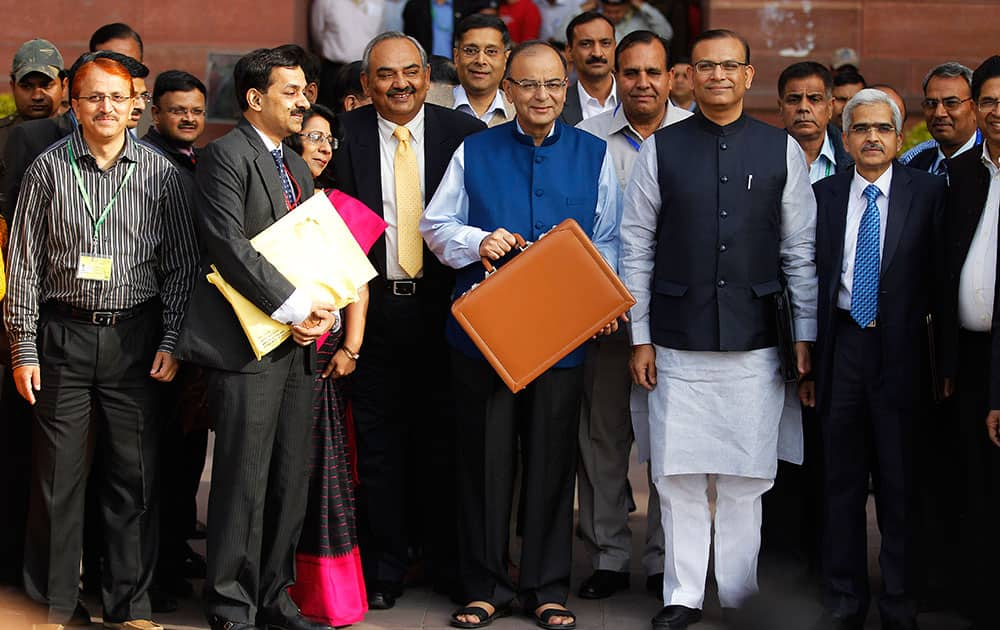 Finance Minister Arun Jaitley, center in blue jacket, display a briefcase containing union budget for the year 2015-16 as he leaves his office for Parliament to present the union budget in New Delhi, India.