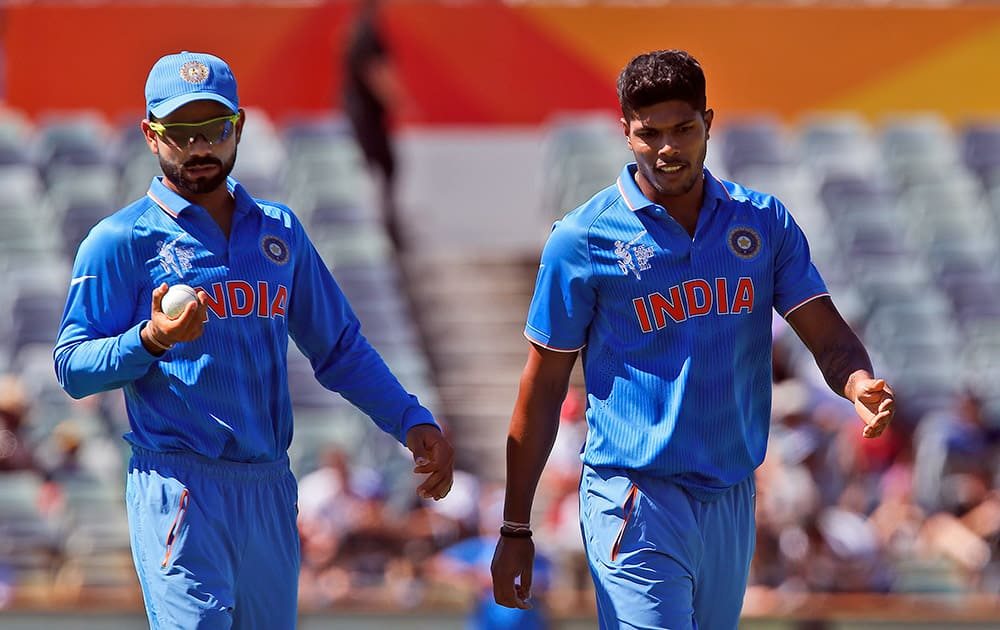 Virat Kohli left, looks at the ball as he walks next to bowler Umesh Yadav during their Cricket World Cup Pool B match against the United Arab Emirates in Perth, Australia.
