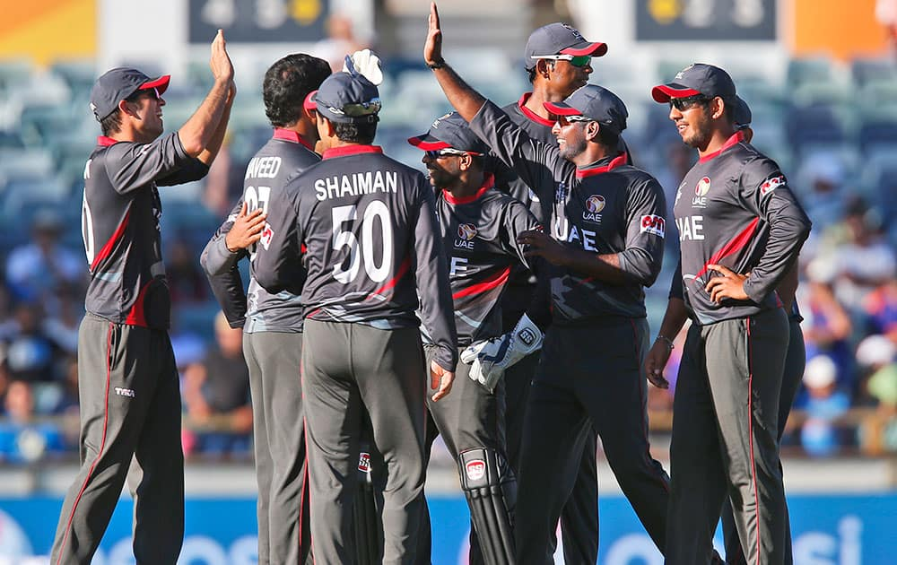 United Arab Emirates team celebrates taking the wicket of India's Shikhar Dhawan during their Cricket World Cup Pool B match in Perth, Australia.