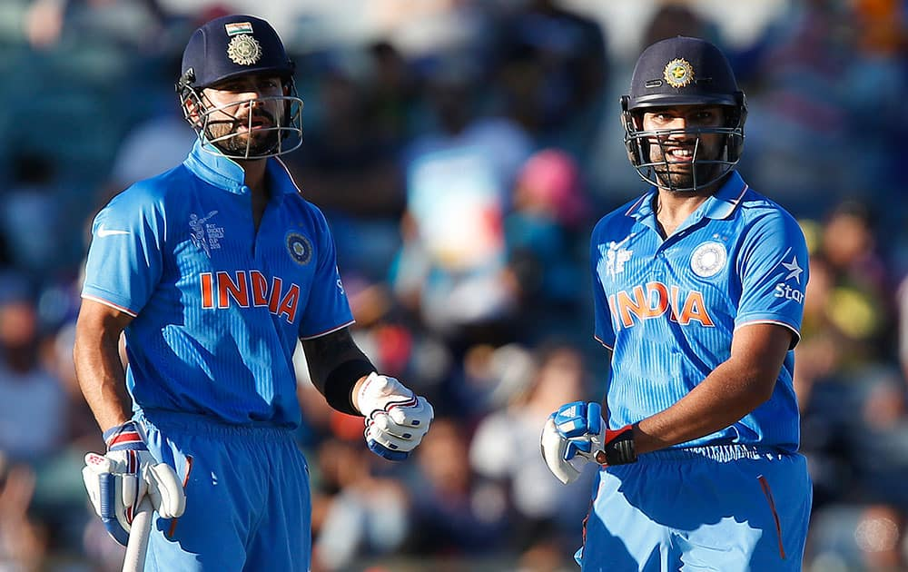 India's Virat Kohli left, and Rohit Sharma chat at mid wicket during their Cricket World Cup Pool B match against the United Arab Emirates in Perth, Australia.