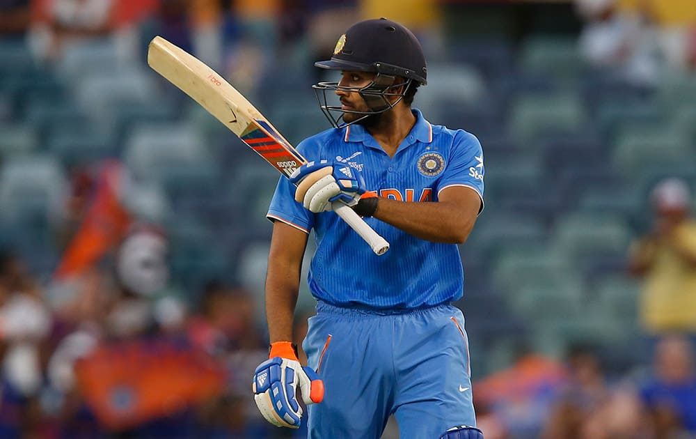 Rohit Sharma raises hit bat after hitting a half century during their Cricket World Cup Pool B match against the United Arab Emirates in Perth, Australia.