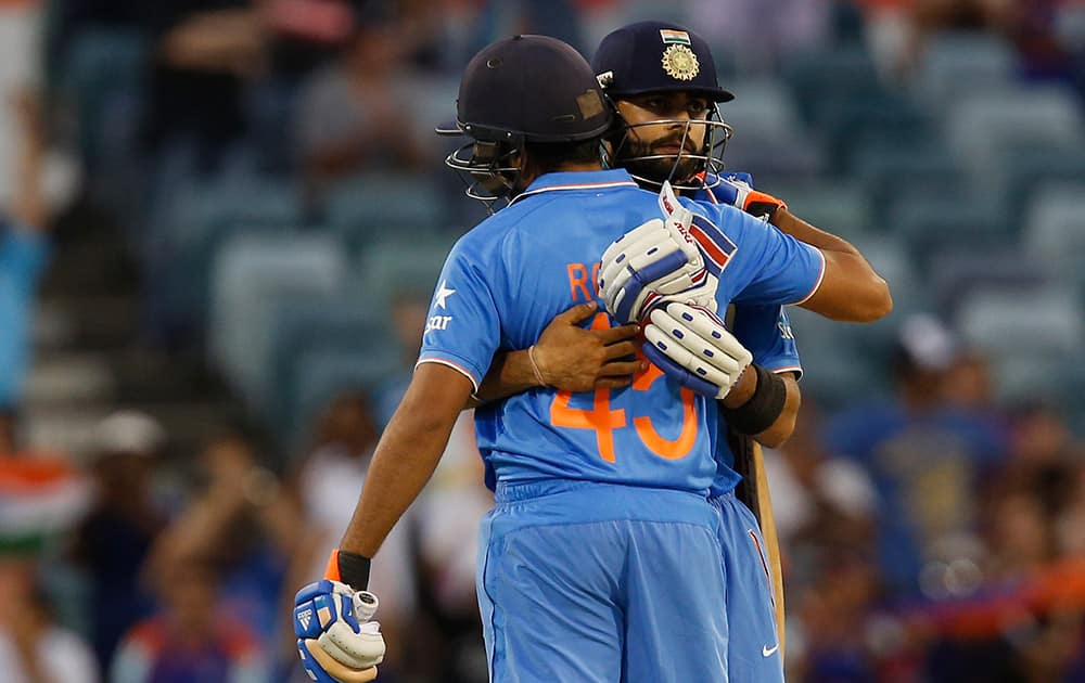 Virat Kohli and Rohit Sharma embrace after they won their Cricket World Cup Pool B match against the United Arab Emirates in Perth, Australia.