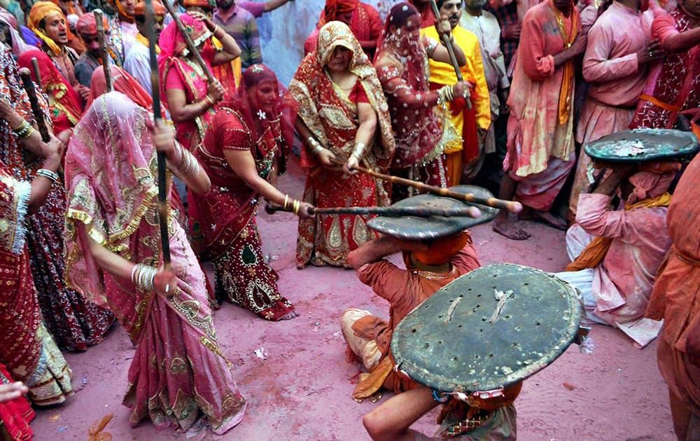 People perform the Lathmaar ritual during the Holi celebrations at Sri Ji temple in Barsana.