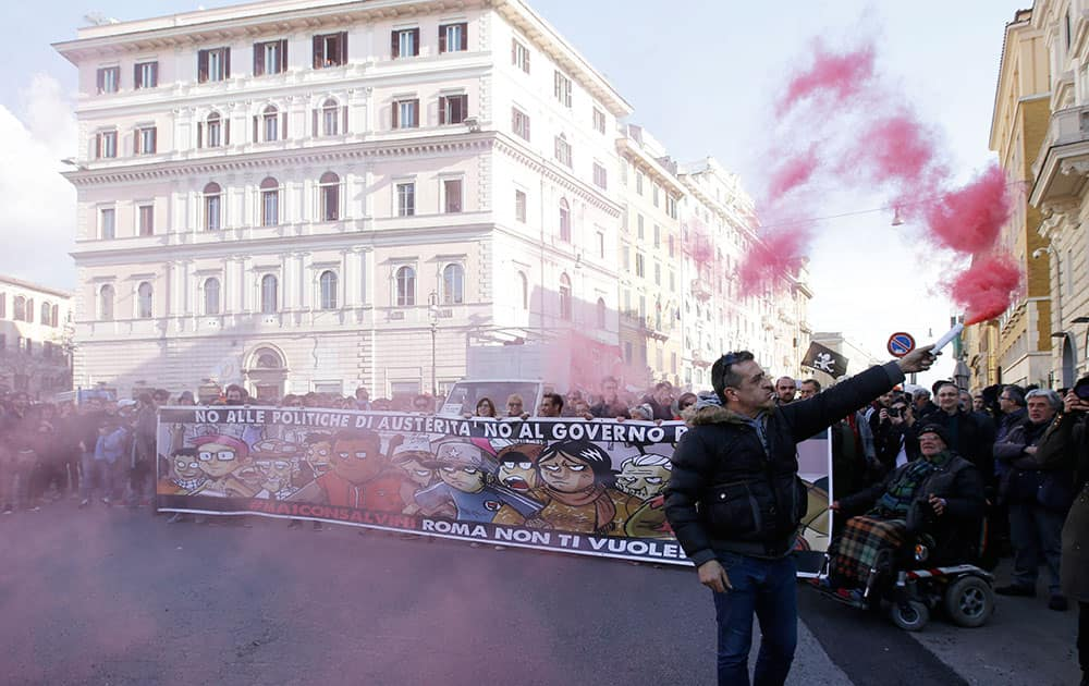 vDemonstrators hold up a banner reading in Italian
