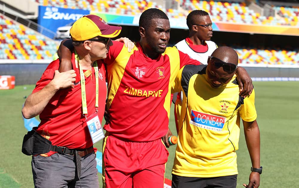 Zimbabwe's Elton Chigumbura, center, is helped off the field after he got injured during the Pool B Cricket World Cup match against Pakistan in Brisbane, Australia.