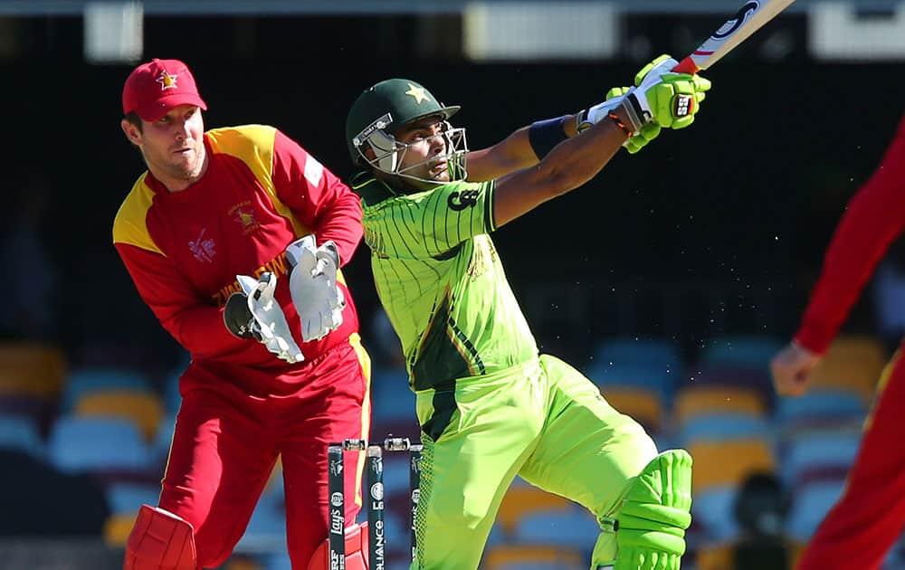 Zimbabwe wicket keeper Brendan Taylor , left, watches Pakistan's Umar Akmal play a shot during the Pool B Cricket World Cup match in Brisbane, Australia.