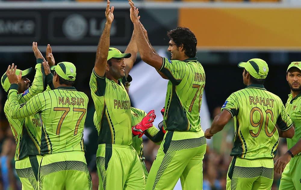 Pakistan players celebrate with wicket of Zimbabwe's Chamunorwa Chibhabha during the Pool B Cricket World Cup match in Brisbane, Australia.