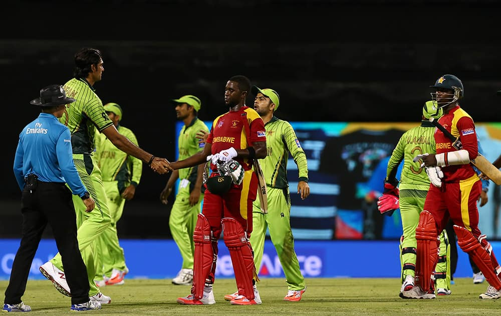 Pakistan's Mohammad Irfan, left, shakes hands with Zimbabwean batsmen after Pakistan won in the Pool B Cricket World Cup match in Brisbane, Australia.