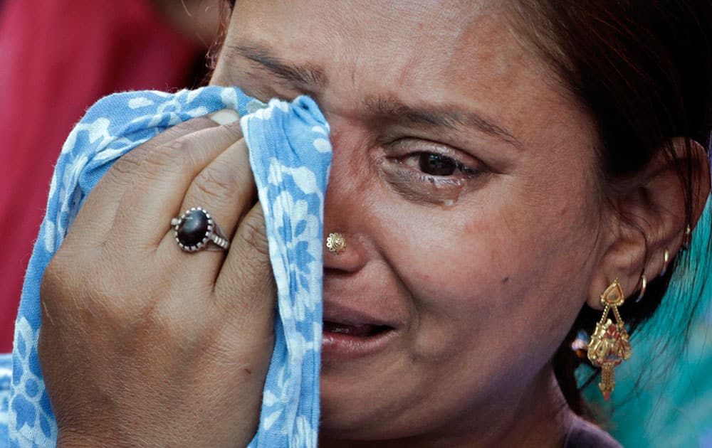 A riot victim wipes her tears during a ceremony marking the anniversary of India`s 2002 anti-Muslim riots, that left more than 1,000 dead, in Ahmadabad.