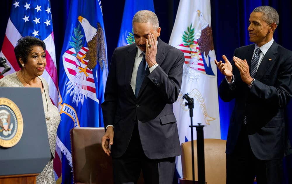 An emotional outgoing Attorney General Eric Holder, center, reacts after singer Aretha Franklin, left, finished singing a song for him, next to President Barack Obama, at an event celebrating Holder at the Department of Justice in Washington.