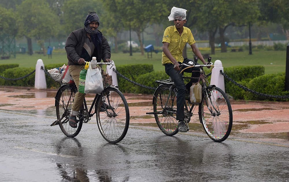 Cyclist at the Rajpath as the national capital received early morning showers in New Delhi.