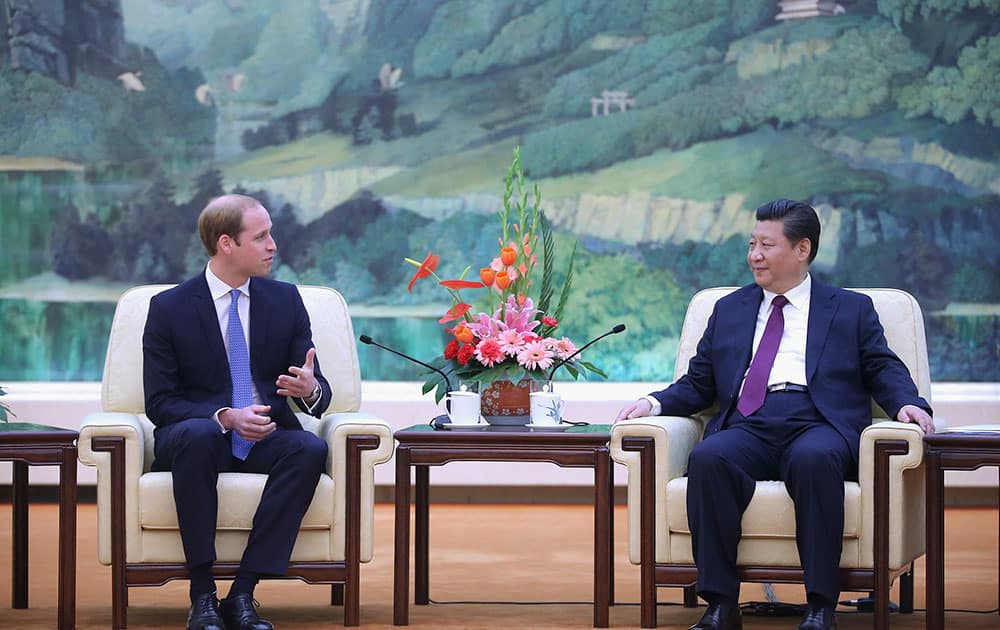 Britain's Prince William, left, meets Chinese President Xi Jinping at the Great Hall of the People in Beijing.