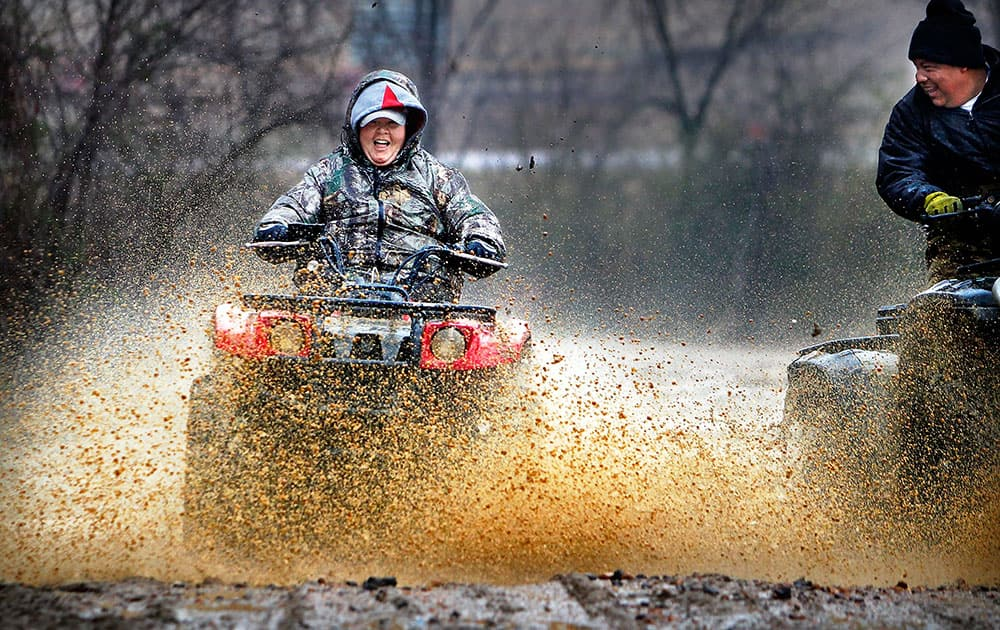 While much of Memphis stayed indoors out of the drizzling cold rain, Vallorie Higgins, left, and Omar Tellez take advantage of the wet day to fly through mud holes along Covington Pike near the Wolf River in Memphis, Tenn.