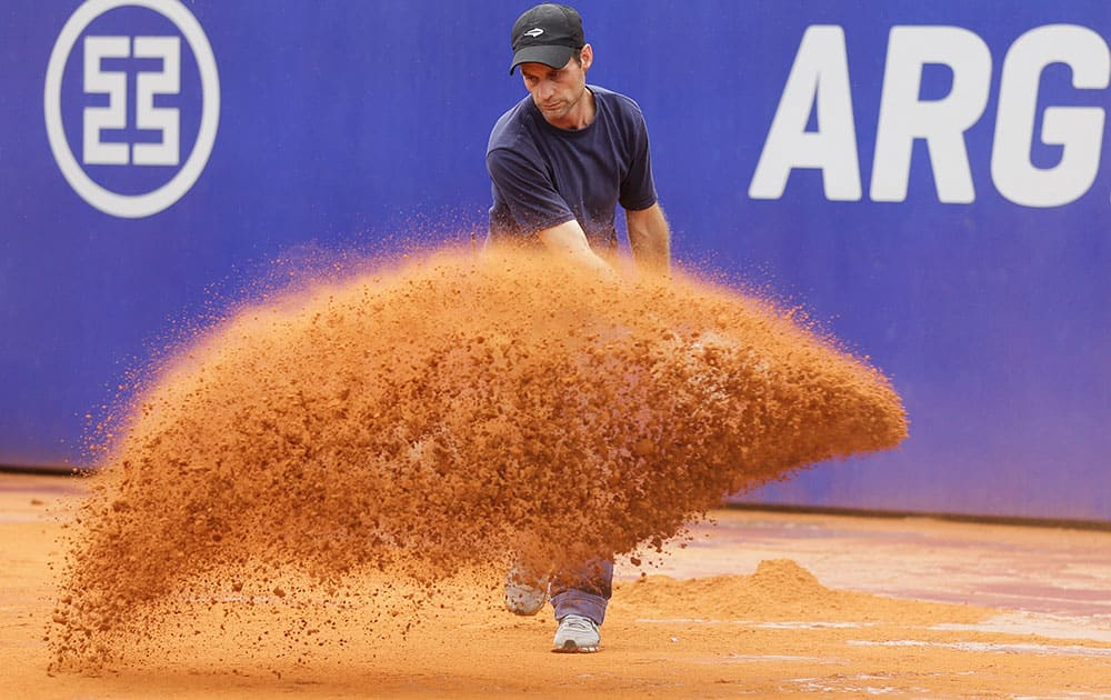 A worker adds dry clay to the court during a rain delay at Argentina's ATP Open final tennis match between Rafael Nadal of Spain and Juan Monaco in Buenos Aires, Argentina.
