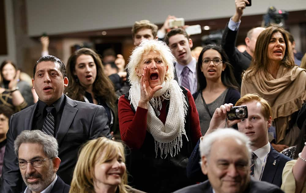 Audience members shout back at demonstrators with the activist group Codepink as they disrupt an event hosted by an organization fighting discrimination against Jews just before a panel discussion with Holocaust survivor Elie Weisel and Sen. Ted Cruz, R-Texas, on Capitol Hill in Washington.