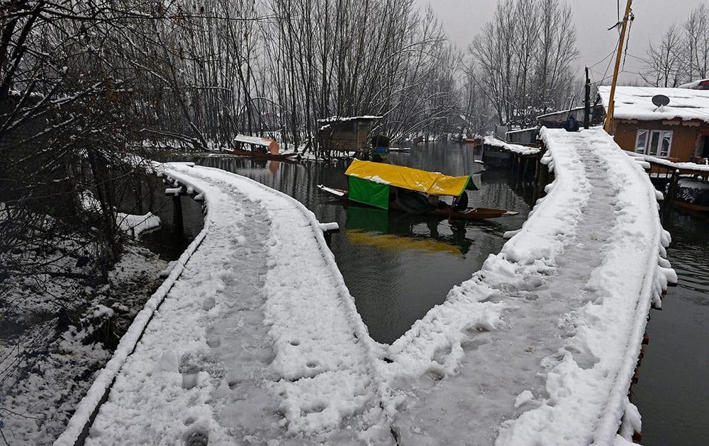 A boatman navigates his Shikara near snow covered bridges at Dal Lake after snowfall.