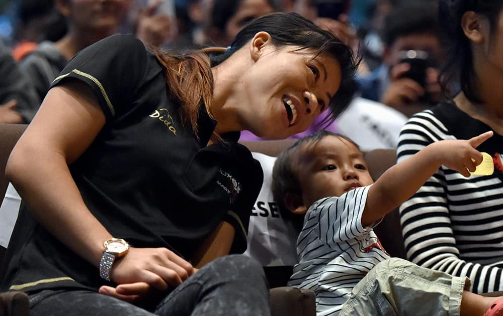 Boxer Mary Kom with her son at a promotional event for Box Out, a social campaign against eve teasing, at IIT in New Delhi.