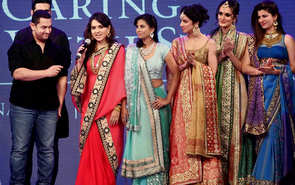 Bollywood actor Aamir Khan with designer Shaina NC and models walks the ramp during a fashion show to raise funds to support children suffering from blood cancer, in Mumbai.