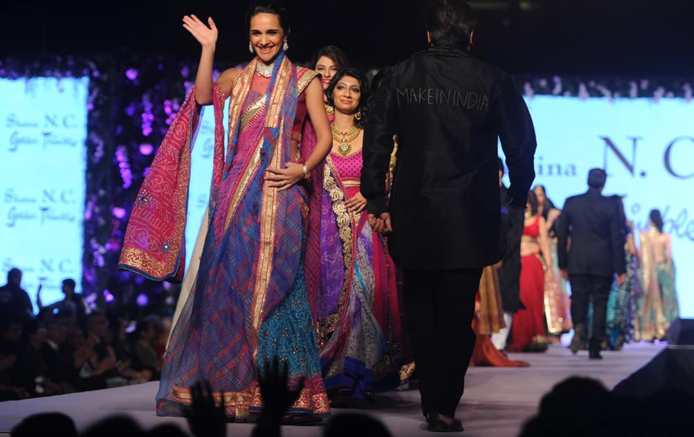 Tara Sharma (L) walks the ramp during the 10th Annual Caring with Style fashion show in association with The Cancer Patients Aid Association to support children suffering from blood cancer in Mumbai. -dna