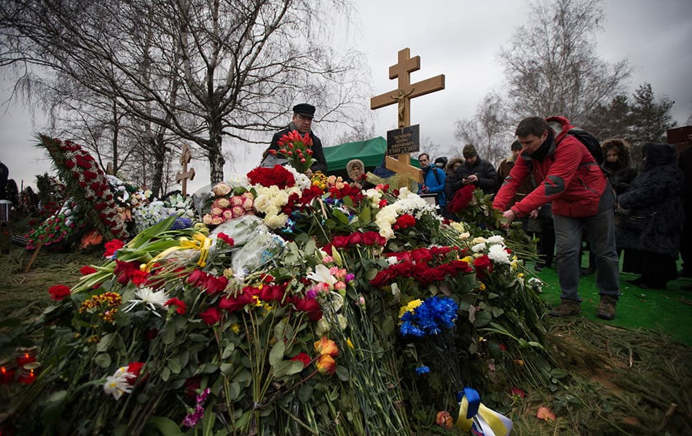 People lay flowers at Boris Nemtsov's grave after a burial ceremony at Troekurovskoye cemetery in Moscow, Russia.