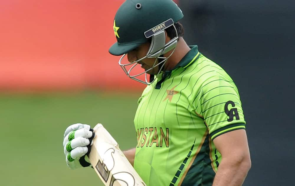 Pakistan's Nasir Jamshed looks at his bat after he was dismissed while batting against the United Arab Emirates during their Cricket World Cup Pool B match in Napier, New Zealand.