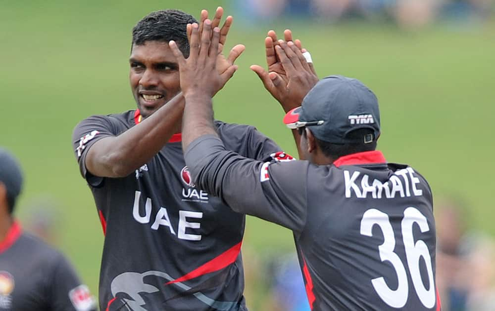 United Arab Emirates K. Karate, right, congratulates teammate Manjula Guruge after taking the wicket of Pakistan's Nasir Jamshed during their Cricket World Cup Pool B match in Napier, New Zealand.
