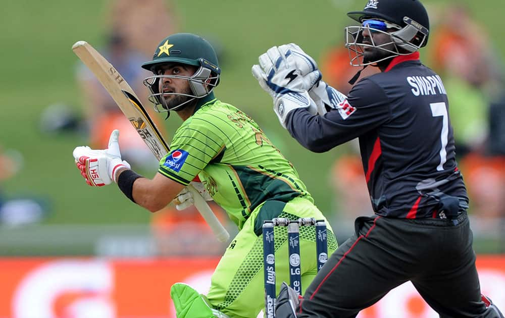 PAKISTAN BATSMAN AHMAD SHAHZAD, LEFT, PLAYS A SHOT AS UNITED ARAB EMIRATES WICKETKEEPER SWAPNIL PATIL WATCHES DURING THEIR CRICKET WORLD CUP POOL B MATCH IN NAPIER, NEW ZEALAND.