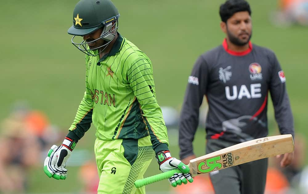 Pakistan's Haris Sohail walks from the field after he was dismissed by United Arab Emirates bowler Muhammad Naveed, right, during their Cricket World Cup Pool B match in Napier, New Zealand.