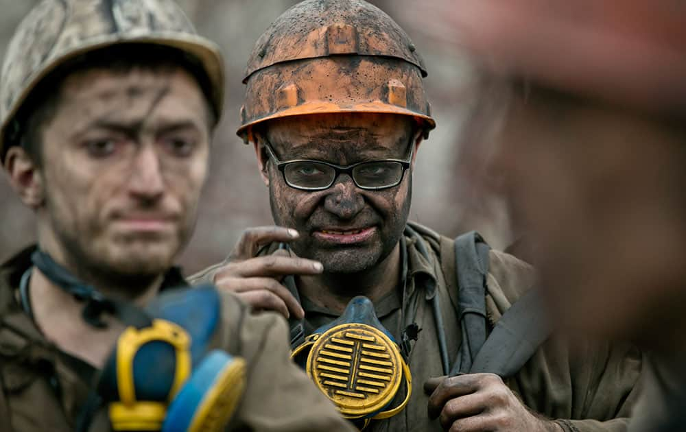 Ukrainian coal miners wait for a bus after exiting the underground of the Zasyadko mine in Donetsk, Ukraine.