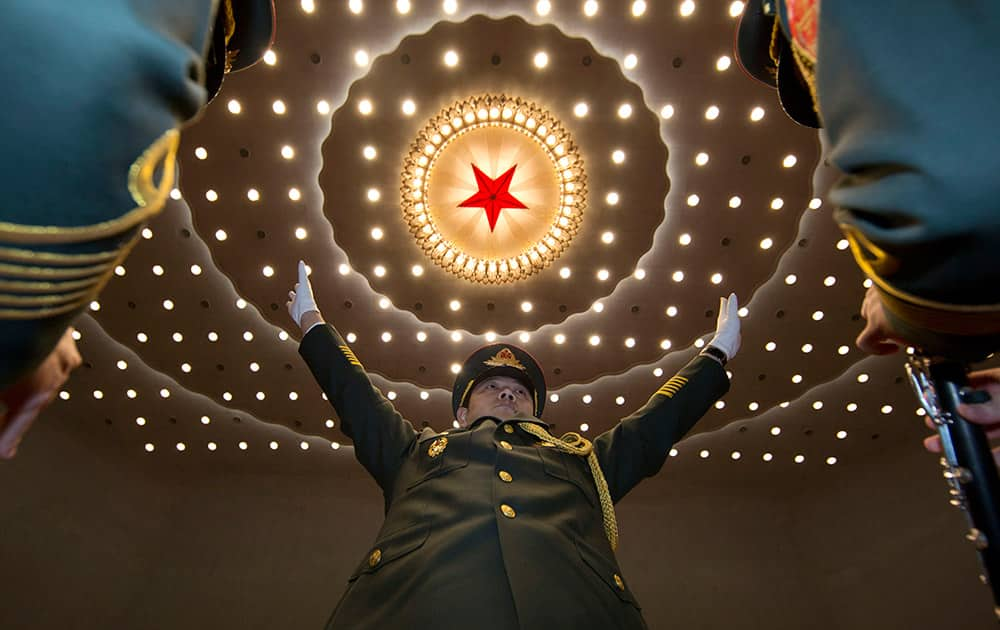 A military band conductor leads during the opening session of the National People's Congress at the Great Hall of the People in Beijing.